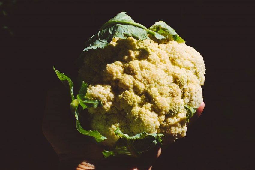 person holding white and green broccoli